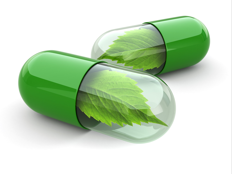 green food supplements capsules with leaves inside